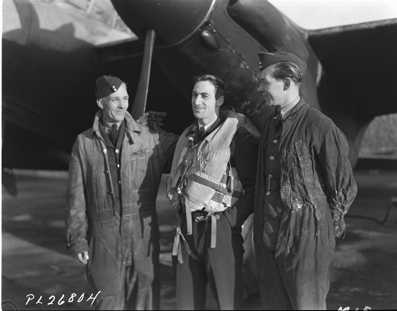 The members of RCAF ground crew are just as proud of their kites as are men who fly them. Shown above are two of the ground crew who have in their care a Mosquito Intruder and the man who flies it. Left to right: Cpl. J.L. Jones, F/L C. Scherf, and LAC R. W. Weighill. They are members of a Canadian Squadron commanded by W/C D.C.S. MacDonald. Janury 21st, 1944 (Source: Royal Canadian Air Force Museum - Researcher: Bill Nurse)