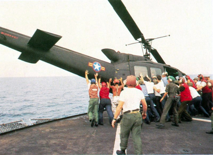 A South Vietnamese UH-1 is pushed overboard on the USS Midway in 1975