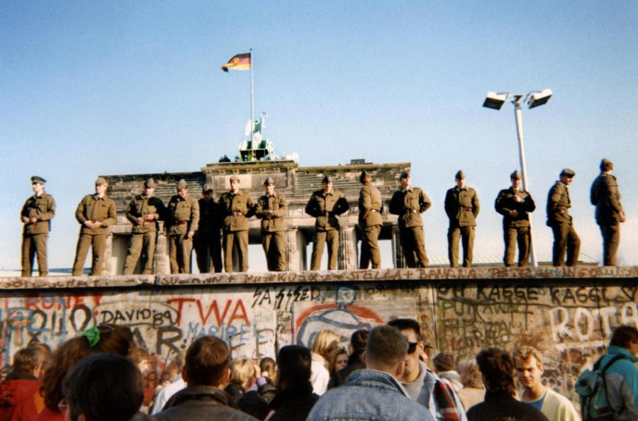 East German border guards stand on a section of the Berlin wall with the Brandenburg gate in the background on November 11th, 1989