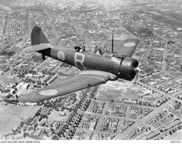 CAC Wirraway (A20-21) of RAAF No. 21 Squadron flying over Melbourne circa February 1940. The pilot of this aircraft is Flying Officer D.J. Doughty and the gunner is Sergeant Ellis (Photo Source: Australian War Memorial)