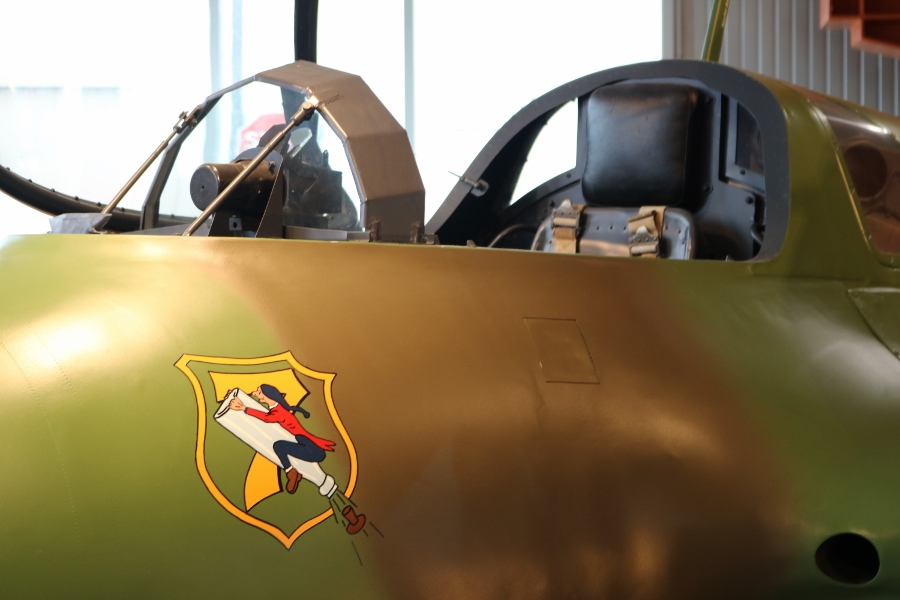 The bullet proof glass in the cockpit of the Me 163B and the 7 Staffel (squadron) of JG 400 emblem showing Baron Münchhausen flying skyward on an uncorked champagne bottle